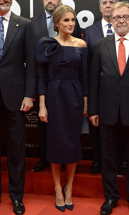 Queen Letizia of Spain wore designer Delpozo for the first time, choosing a dark blue off-the-shoulder look for the <I>As</I> sports newspaper 50th anniversary dinner at the Palacio de Cibeles in Madrid on December 4. The tailored dress, which the royal wore with matching heels, featured an architectural oversized rose detail on one shoulder. 