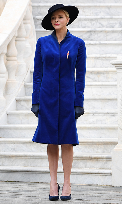 During Monaco National Day in November 2017, Princess Charlene of Monaco donned a bespoke coat in cobalt blue velvet by one of her favorite labels, Akris. She finished off the look with a wide-brimmed hat and dark blue shoes and leather gloves. 
