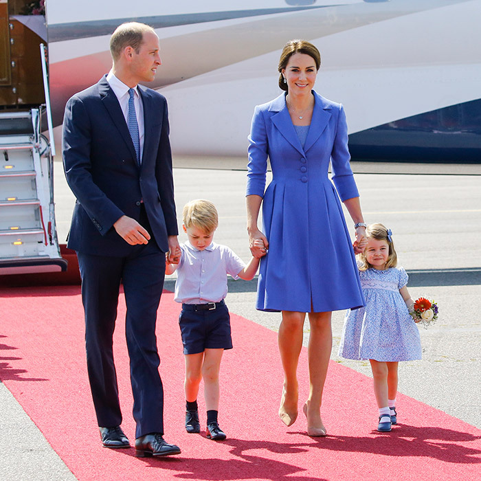 On day one of the German visit on July 19, 2017, William, Kate, George and Charlotte stepped off the plane in Berlin matching wearing various shades of blue. (Mom Kate wore a coat dress by Catherine Walker.) The fact that little Charlotte was clutching a tiny bouquet sent the cute factor sky high!