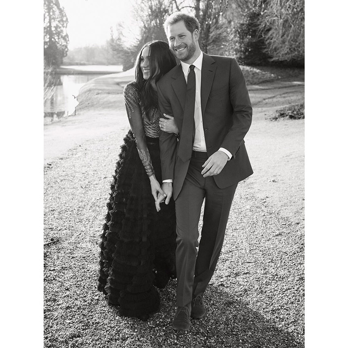Shortly after the release of the first two images, Kensington Palace released a third candid photo of Harry and Meghan walking through the castle grounds. In the photo, the bride-to-be, wearing Ralph & Russo haute couture, holds her future husband close as they stoll hand in hand. 