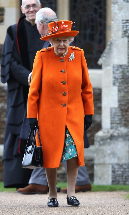 Queen Elizabeth II wore a cheery orange coat and matching hat, along with a green floral dress, and her trusty loafers and handbag, for the traditional Christmas Day service at the Church of St Mary Magdalene in King's Lynn, England. Once again, the monarch was surrounded by her nearest and dearest for the special day.