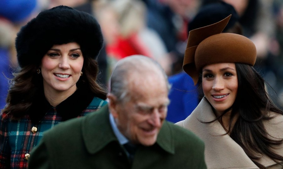 Duchess Kate, wearing a fur hat, and Meghan, sporting a creation by Philip Treacy, chatted with one another as they walked up to the church gates. 