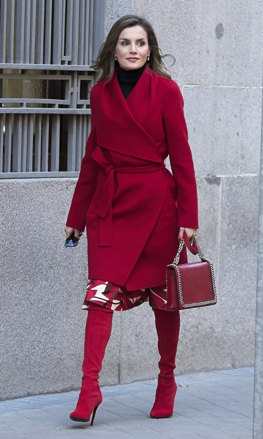 Queen Letizia of Spain looked ready for the holidays in her vibrant red ensemble! The Spanish queen wore a BOSS Hugo Boss wrap coat worn with high-heeled red suede boots and a Zara purse.
