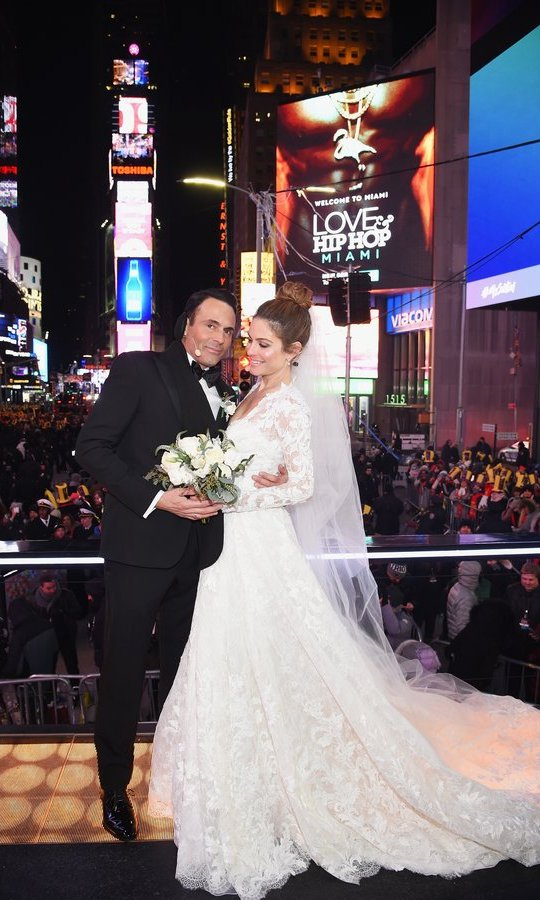 "For her ceremony in Times Square, Maria Menounos wore the stunning lace 'Randala' gown from the Atelier Pronovias 2018 Collection. ""You have to think you're outside in Times Square, it's freezing, you need something beautiful but appropriate,"" she told People of choosing a gown. Her final choice, she said, ""took my breath away"".