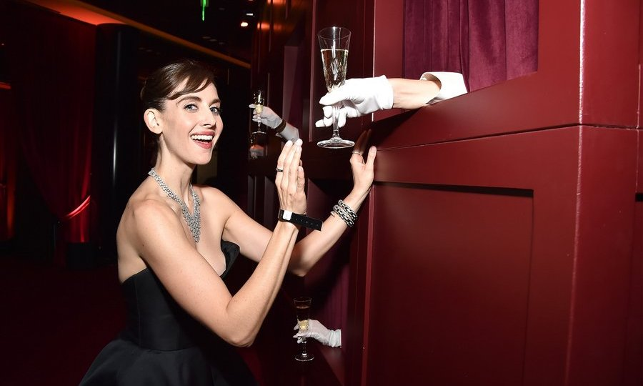 Don't mind if I do! Alison Brie gets ready to toast the evening at the Netflix Golden Globes after party.
