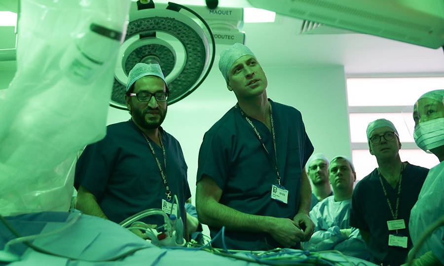 The doctor is in! Prince William suited up in scrubs to watch in lead surgeon Asif Chaudry, left, and colleague surgeon Myles Smith in action prior to a highly complex robotic cancer operation during his visit to The Royal Marsden Hospital on January 10.
