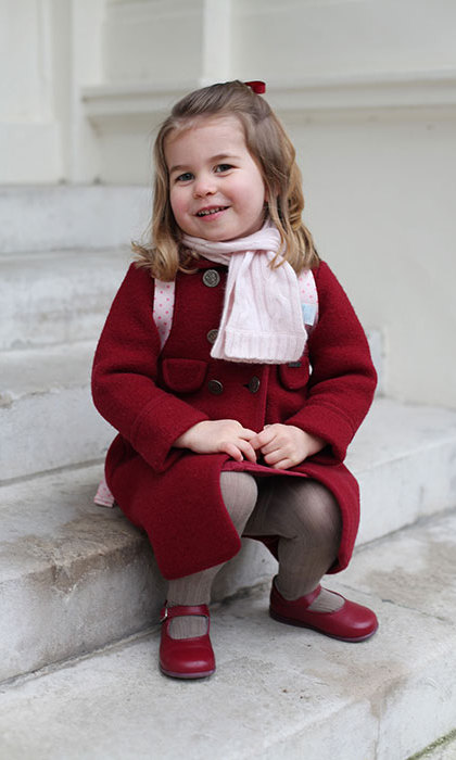 In a second photo, Charlotte, who is wearing a red bow in her hair and is carrying a pink backpack, sits on some steps as she gives her mom an adorable grin.