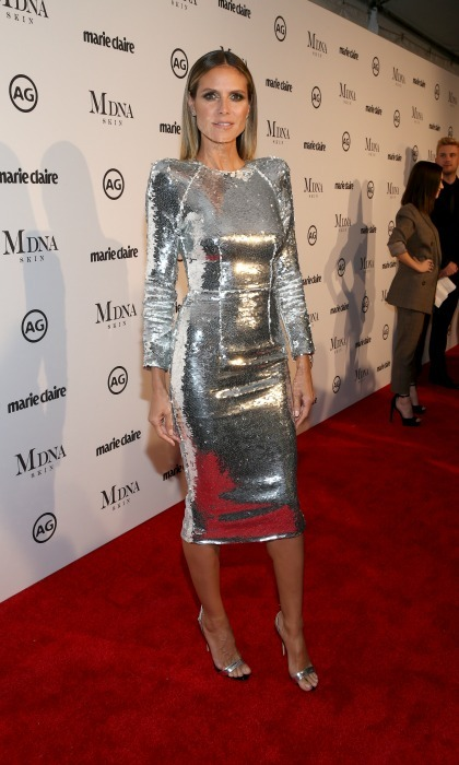 Heidi Klum dazzled at the outing in a long sleeve metallic number. The tight dress hugged the model's enviable figure as she posed for photos on the carpet. Heidi opted to wear her gorgeous blonde locks down and complimented the frock with silver heels.