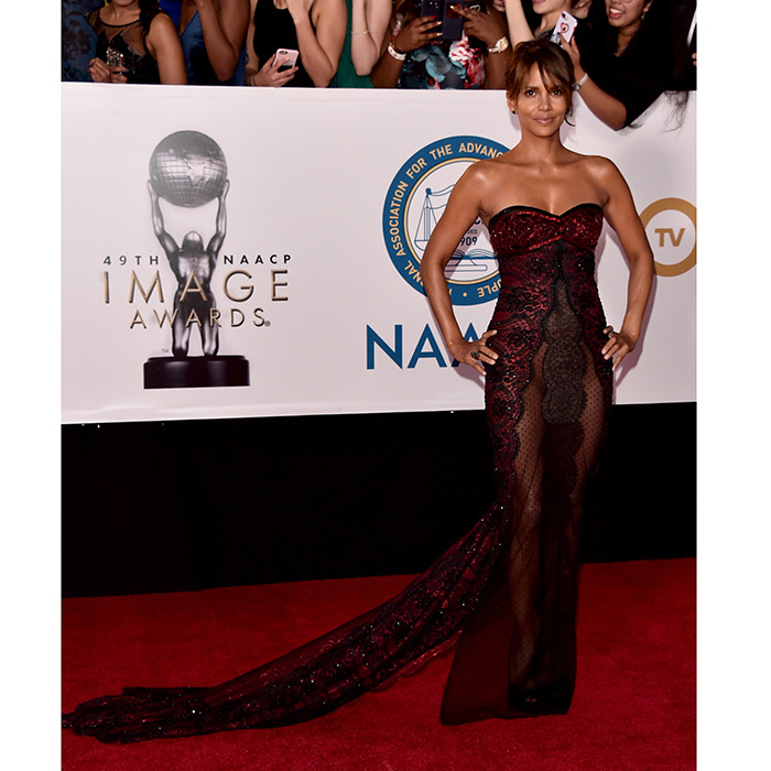 Halle Berry showed her signature daring style in a red and black lace Reem Acra gown with sheer panels.