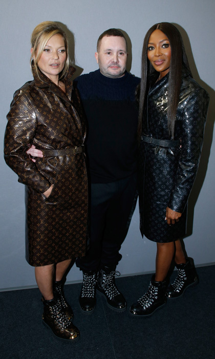Kate Moss and Naomi Campbell wore matching trench coats as they posed with stylist Kim Jones after the Louis Vuitton menswear show in Paris.