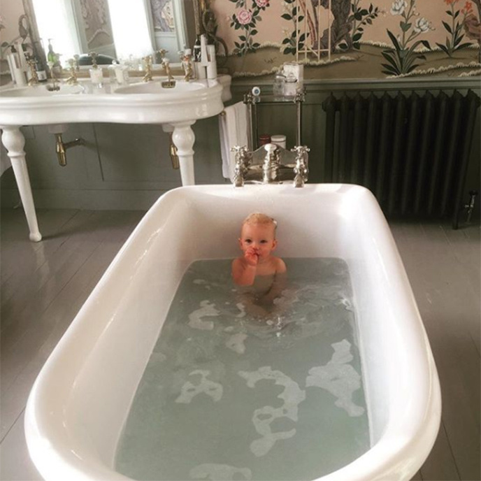 Celebrity chef Jamie Oliver's little boy River gets to take relaxing soaks in the family's elegant freestanding bath. Glance behind him and check out their beautiful double basins. 