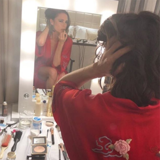 Victoria Beckham's Hollywood mirror takes center stage as she gives us a glimpse at her dressing table. If you look behind her in the mirror, you can see her luxurious-looking bed with a tufted headboard.