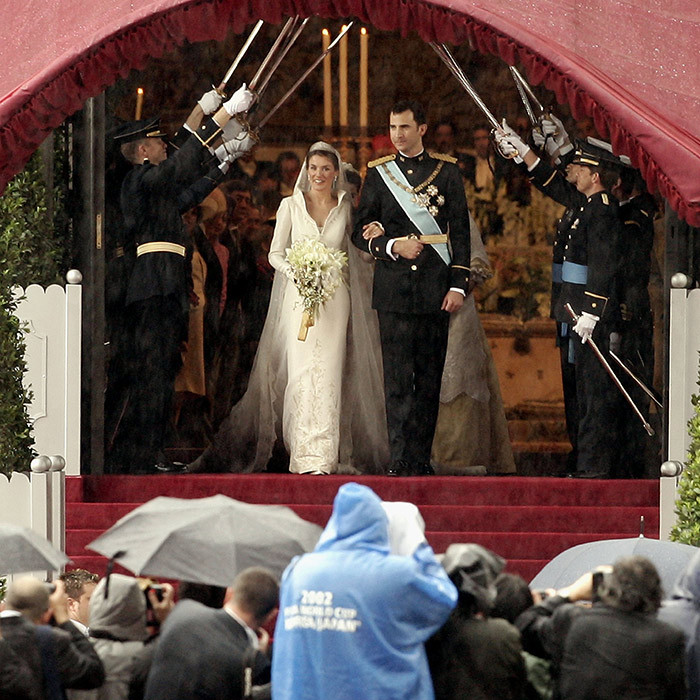 Emerging from the cathedral, the newlyweds were greeted with a military salute as well as cheers from the crowds who had been outside weathering the rain. 