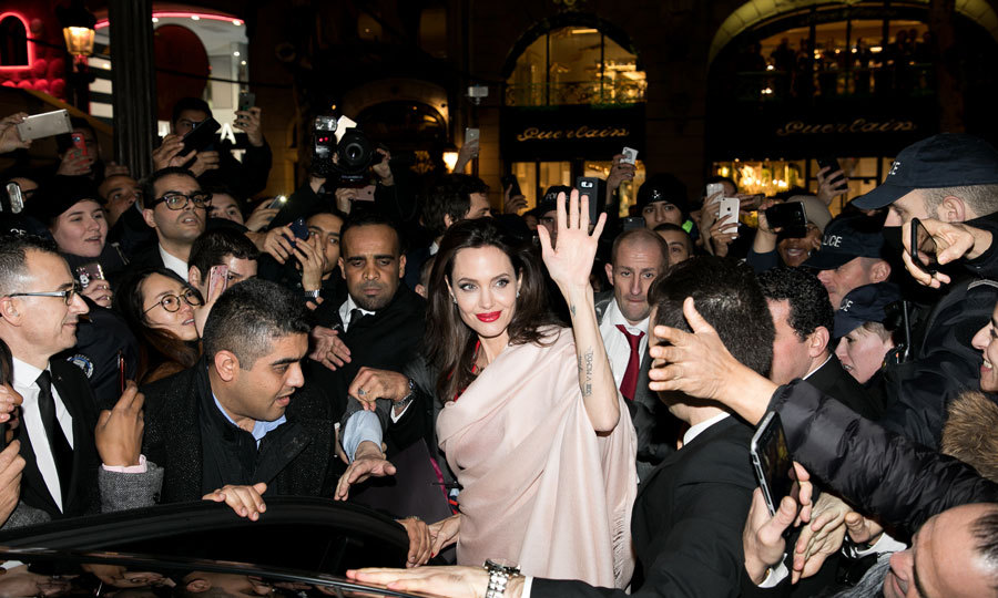 Angelina Jolie's star power was on display as she left a Guerlain store on Paris' famed Champs-Elysees. The actress, who is the face of the brand, wore a red lip and beige shawl for the outing.
