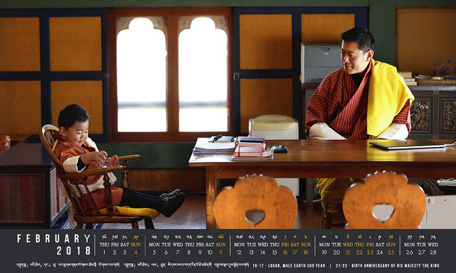 In the run up to little Prince Jigme Namgyel Wangchuck's February 5 birthday, the royal family's Facebook page shared the new page of the monthly calendar. In the calendar photo the adorable young Prince is seen sitting at a desk with his father, the reigning Dragon King of Bhutan, in His Majesty's office.