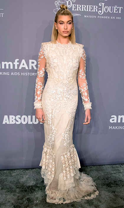 Hailey Baldwin hit the red carpet wearing a embroidered lace gown with illusion sleeves.