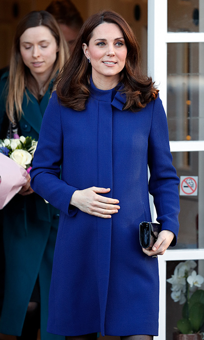 Wearing a royal blue coat by Goat, the pregnant Duchess Of Cambridge cradled her bump at the Action On Addiction Community Treatment Centre in Wickford, England on February 7.