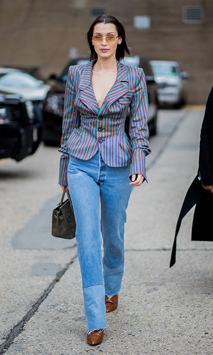 Heading to Ralph Lauren, Bella Hadid rocked another take on the off-duty model look with boyfriend jeans and a candy-colored striped peplum jacket. 