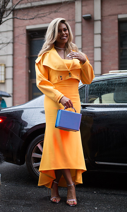What rain? Laverne Cox wore a cheery citrus outfit – a bright orange dress and cropped jacket – to the Christian Siriano show. 