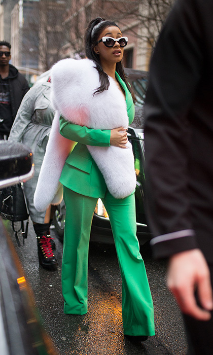 Woman of the moment Cardi B showed her serious street style finesse in a green suit and furry stole outside Christian Siriano.