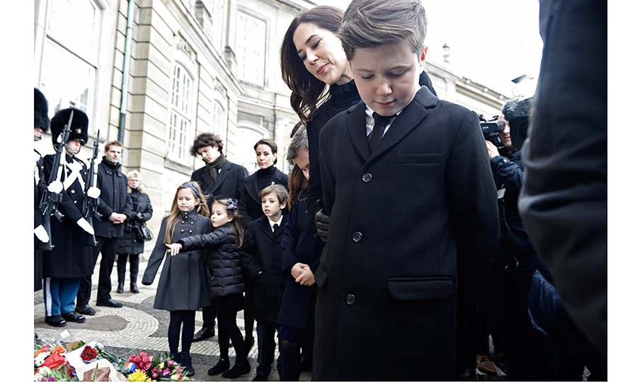 Also there to help guide the young Princes and Princess as they publicly mourned their grandfather was Henrik's daughter in law, Crown Princess Mary, wife of Crown Prince Frederik. Here, with Princess Marie and Henrik's grandchildren seen in the background, Mary and Prince Christian look at the floral arrangements left by well-wishers.