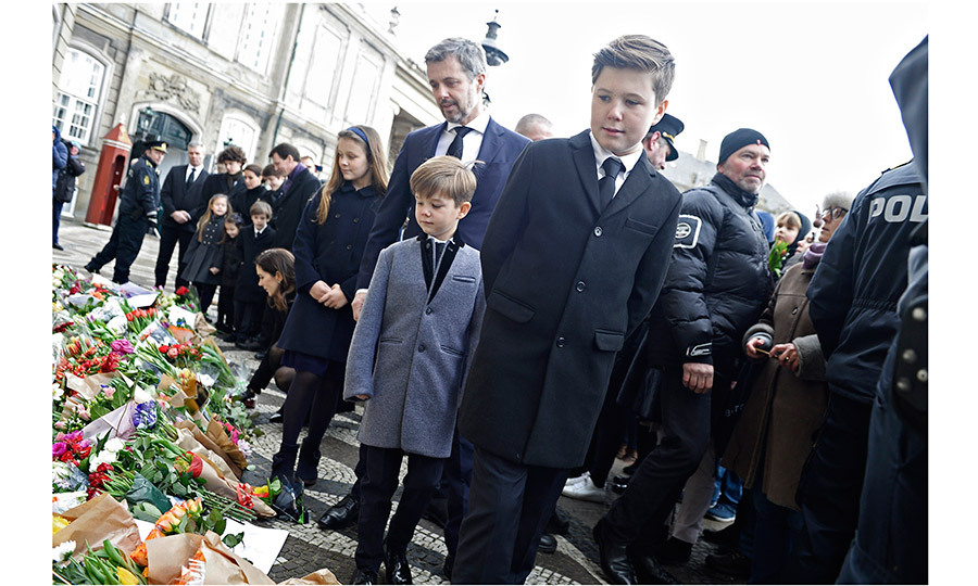 Here Crown Prince Frederik is seen with his 12-year-old son, second-in-line Prince Christian, seven-year-old son Prince Vincent, and ten-year-old daughter Princess Isabella, as they look at flowers left by mourners in front of Amalienborg Palace on February 15. Behind them are Crown Princess Mary, kneeling, as well as Henrik's younger son Prince Joachim with his children and wife Princess Marie.