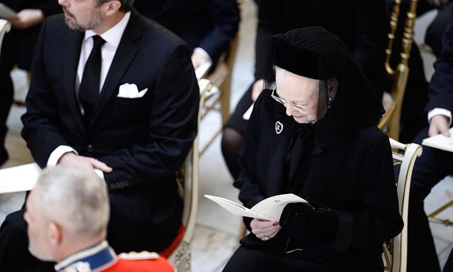 Queen Margrethe, wearing a dark coat, brooch and hat with veil, seemed calm and serene surrounded by her family.