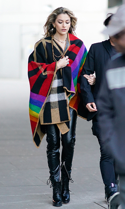 Michael Jackson's daughter and LFW guest Paris Jackson wrapped up in a multicolor cape and zipped leather trousers. 