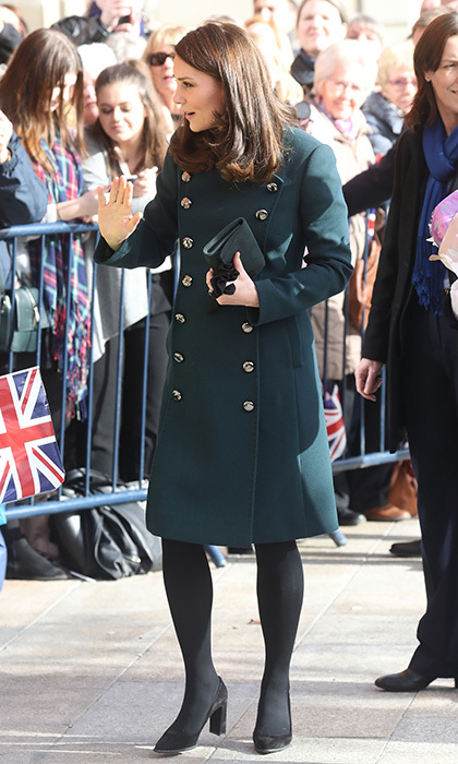 On February 21, 2018, Duchess Kate traveled to Sunderland, in North East England, with her husband the Duke of Cambridge. Pregnant Kate stunned in a dark green military style coat by Dolce & Gabbana, teaming her ensemble with high-heeled shoes, a simple clutch bag and delicate jewelry. 