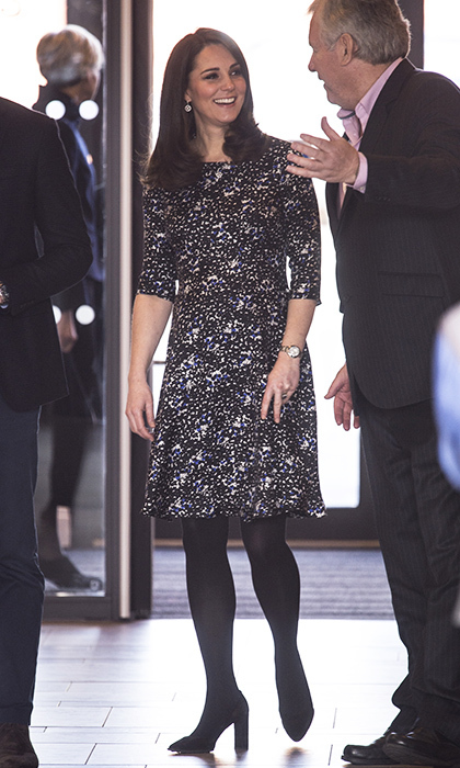 Underneath the green Dolce & Gabbana coat the Duchess wore a black and violet floral dress with mid-length sleeves by one of her favorite maternity designers, Seraphine.
