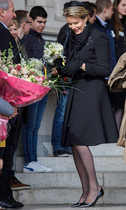 An elegant Queen Mathilde of Belgium accepted flowers from the crowd before mass at Our Lady Church in Brussels.