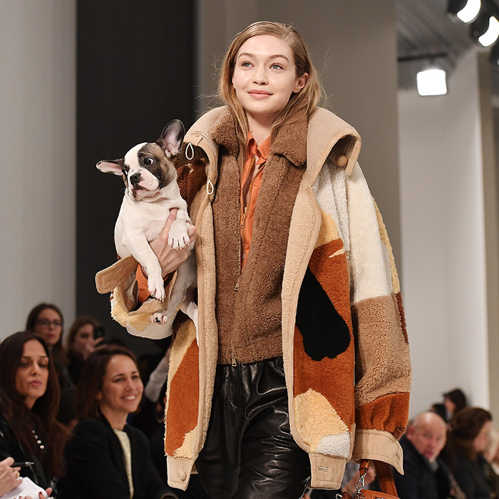 The only thing sweeter than the natural makeup at the Tod's show was the parade of pups that took to the runway. Here's Gigi Hadid toting an adorable little pal on the 'dogwalk' on February 23.