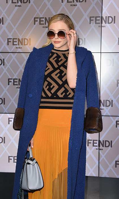 It's all about the shades! Chloë Grace Moretz arrived at the Fendi show with a navy blue coat draped over her shoulders and a pair of decorated round sunglasses. 
