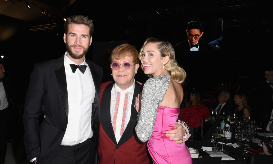 Miley Cyrus and her leading man Liam Hemsworth cozied up with Elton John during his 26th annual AIDS Foundation Academy Awards viewing party with cocktails by Clase Azul Tequila.