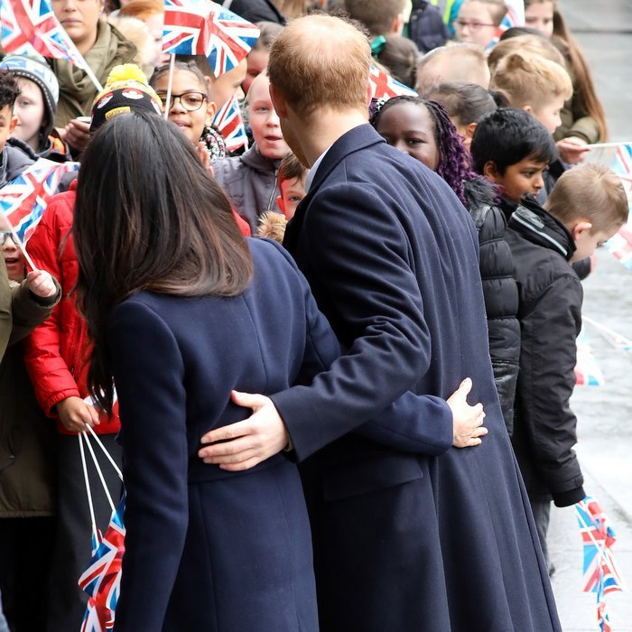 Meghan and Harry showed off one of their signature mutual  hand-on-the-back gestures as they greeted well-wishers.