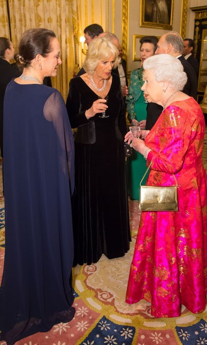 The 91-year-old Queen looked elegant in a pink and orange silk evening gown and gold metallic purse.