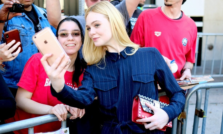 But first, let's take a selfie! Dakota's sister Elle Fanning looked fabulous in a pinstripe jumpsuit while greeting a fan at the premiere of her film <i>Galveston</i> at the Paramount Theatre on March 10. 