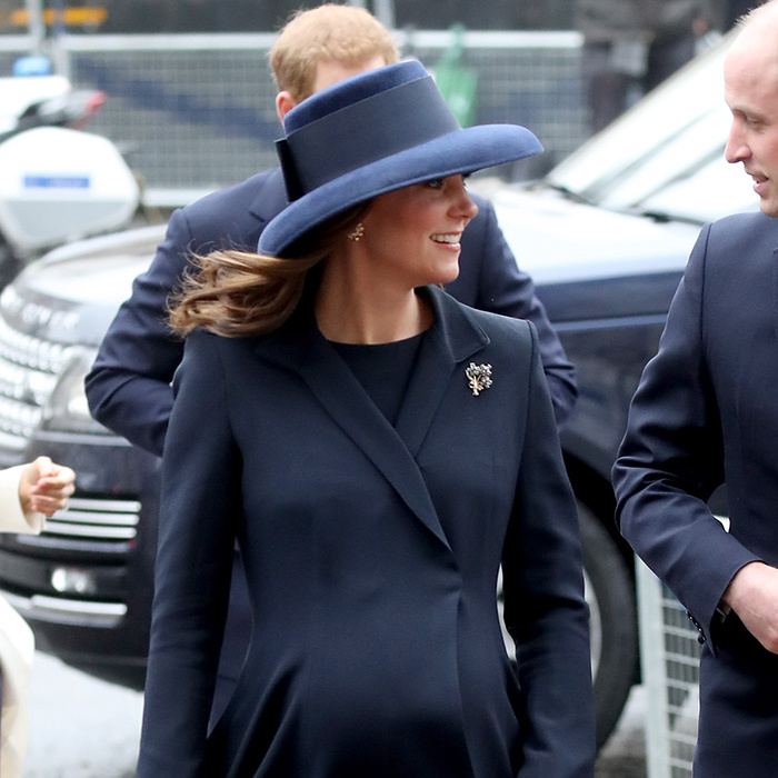 The Duchess accessorized her ensemble with sparkling earrings and a brooch, and a wide-brimmed navy blue hat by Lock and Co.