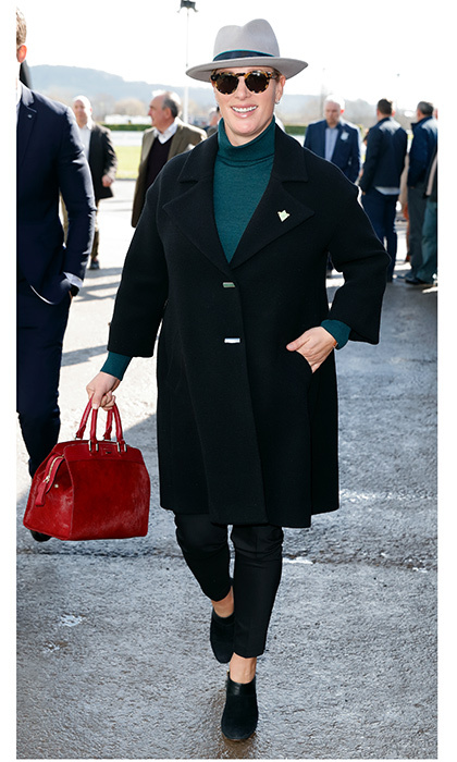 Zara Tindall kept her bump under wraps in a black coat at Cheltenham a day earlier, sporting a grey fedora and lending her outfit a pop of color with a red handbag.