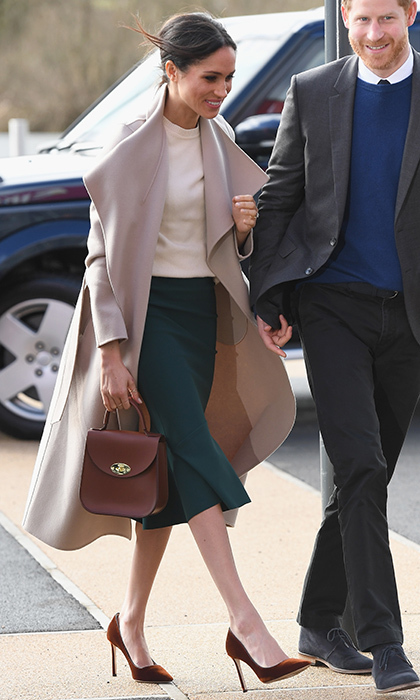 On March 23, Meghan and her fiancé Prince Harry headed to Northern Ireland for a packed day of official engagements. The former <I>Suits</I> star looked sharp in a dark green pencil skirt from Canadian label Greta Constantine, a cream sweater by Victoria Beckham and coat by Mackage. Meghan accessorized with velvet Jimmy Choo shoes and one of her statement pieces – a top handle bag – this time a chic chestnut Bloomsbury bag by British designer Charlotte Elizabeth in brown leather.