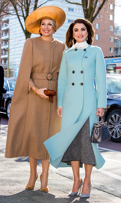 During King Abdullah II and Queen Rania Of Jordan's official visit to the Netherlands, the Jordanian Queen and Dutch Queen Maxima were synchronized in tailored style. While Maxima wore a tan belted cape-style coat, Rania went for spring hues in a double-breasted style in Tiffany blue. The two were on a visit to the Gemeentemuseum in The Hague.