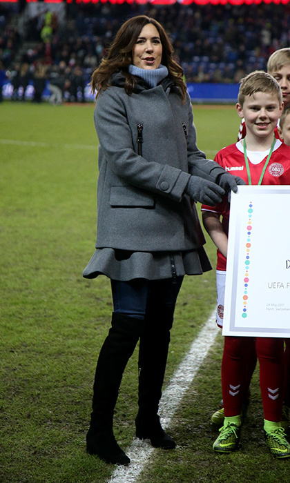 Crown Princess Mary of Denmark kept warm in a grey flannel coat and thigh-high boots as she received a 50,000 euro check (around $62,000), on behalf of her charitable foundation, from the Danish Football Association. The exchange took place before the international friendly soccer match between Denmark and Panama in Brondby, Denmark. 