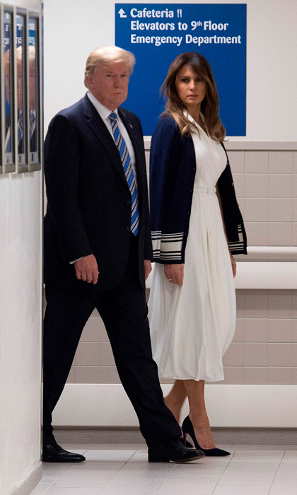 The first lady met first responders at Broward Health North Hospital in Pompano Beach, Florida following the mass shooting at Marjory Stoneman Douglas High School. Melania wore a white dress and cardigan both by Ralph Lauren for the somber outing. 