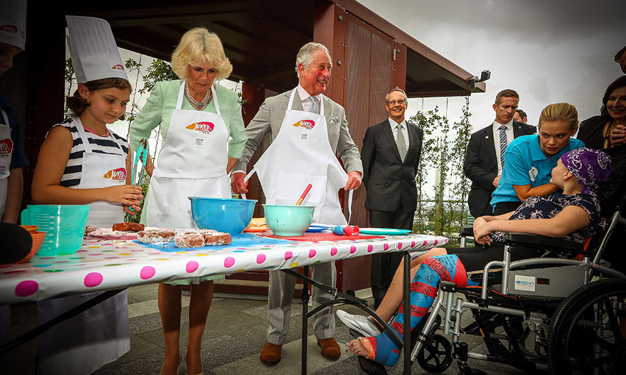 Let's get cooking! Prince Charles and Camilla helped prepare lamingtons, a type of Australian cake, with Elizabeth Ross, nine, and  12-year-old Max Bishop at the Lady Cilento Children's Hospital.
