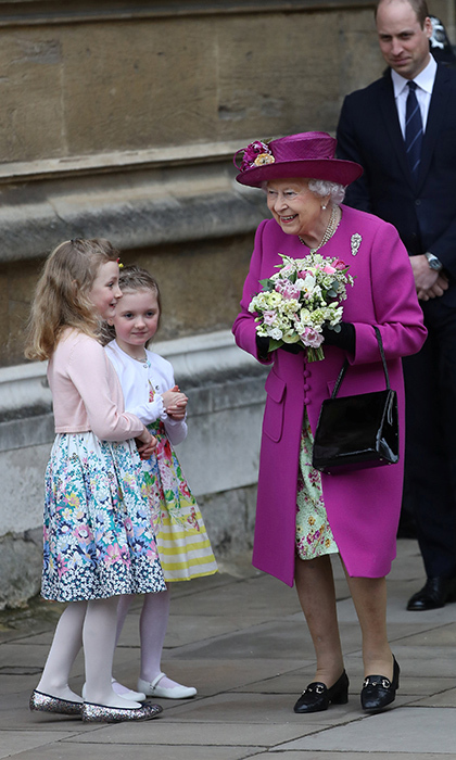 With grandson Prince William smiling behind her, Queen Elizabeth II was greeted by adorable little girls bearing flowers after the Easter Mattins Service at St George's Chapel at Windsor Castle.
