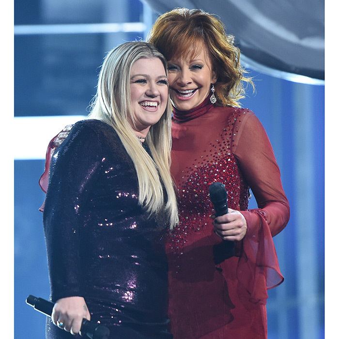 Reba McEntire and daughter-in-law Kelly Clarkson reunited on stage to sing Reba's 1993 hit <I>Does He Love You</i>.