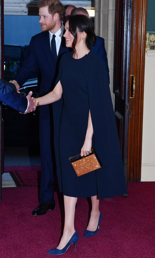 "The former TV star joined Prince Harry and the British royal family for an evening out on April 21 wearing a gorgeous navy cape dress by Stella McCartney. For the event, Queen Elizabeth's 92nd birthday concert, Meghan added a personalized touch of glam by carrying one of her <a href=""https://us.hellomagazine.com/fashion/12018032826440/meghan-markle-purse-top-handle-handbag/1/""><strong>signature top handle purses</strong></a>:  a $1490 Naeem Khan Zodiac clutch with a design honoring her astrological sign, Leo. 