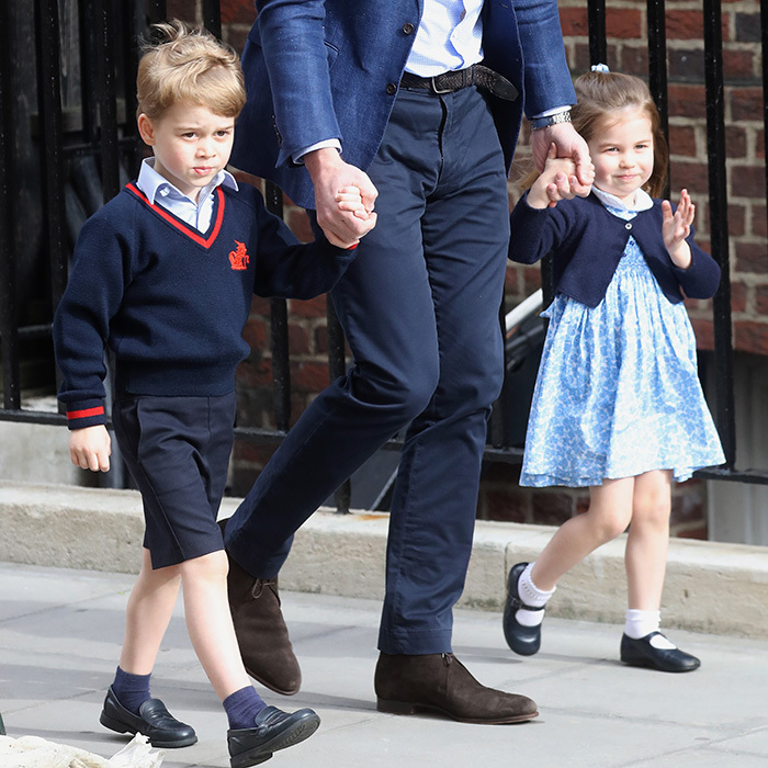 Prince George was still wearing his school uniform for the Monday afternoon visit, while Princess Charlotte had on a blue dress, cardigan, and black Mary Janes.