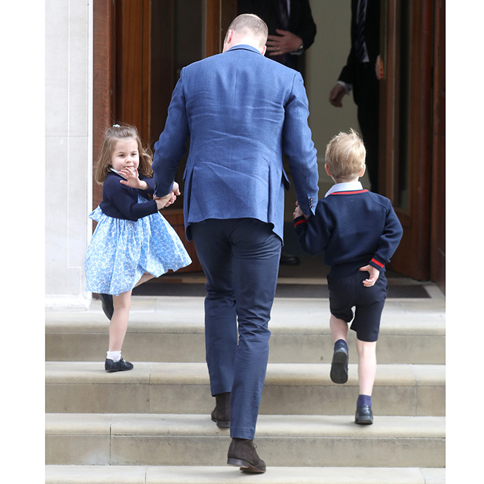 Little Princess Charlotte adorably turned to give photographers and well wishers a royal wave as she, her father and her big brother George headed into the Lindo Wing.