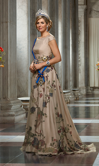 Queen Maxima of the Netherlands was both regal and drop dead gorgeous in a new set of photos released by the Dutch palace to celebrate her husband King Willem-Alexander's five years on the throne. In the formal shot, the Queen wears a beige silk gown with embroidered floral overlay.